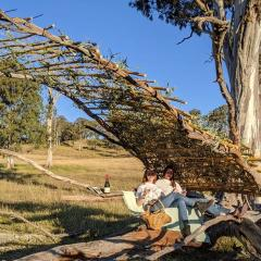 UQ architecture students Siubhan Rudge (L) and Lara Rann (R) sitting under the pavilion they'd constructed by hand using available materials